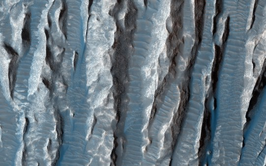 Terreno de yardangs en el hemisferio norte de Marte, en la parte más oriental del sistema de cañones Valles Marineris. Este terreno está moldeado por dos elementos: el viento, que actuó y sigue actuando, y el agua. Antiguos canales de salida de agua fluyeron por esta zona hacia las llanuras del norte marciano. También se oobservan yardangs, porciones de roca provenientes de chorros de arena en crestas delgadas. La fotografía fue tomada en febrero de 2015 por la Mars Reconnaissance Orbiter (Imagen tomada de https://www.nasa.gov/)