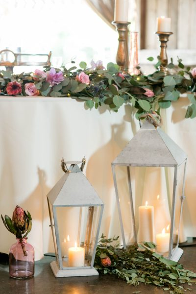 Lanterns and table garlands at a Rustic Chic barn reception. Cotton Creek Barn, Tahoka, Texas. Flowers and planning by Jessica Ormond Events. Photography by Allee J Photography.