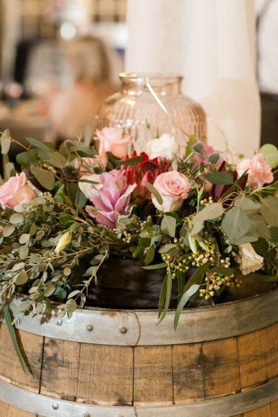 A lantern on a wine barrel with roses, protea, and kale. Rustic chic reception at Cotton Creek Barn in West Texas. Flowers and planning by Jessica Ormond Events. Photography by Allee J Photography.