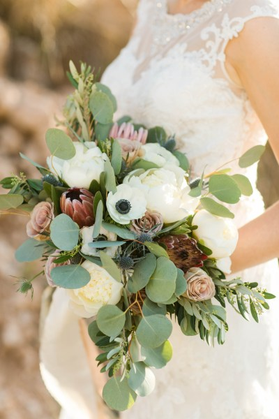 Wild bridal bouquet of protea and thistle created by Lubbock wedding florist Jessica Ormond Events. Photographed by Allee J.
