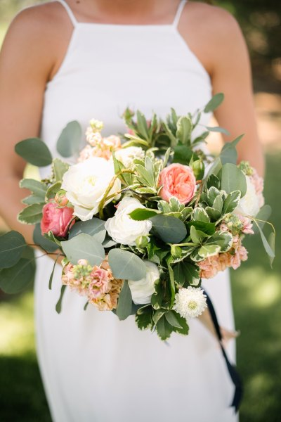 Fresh coral and white summer bridal bouquet of garden roses, Ranunculus, Scabious, Stock designed by Texas wedding florist Jessica Ormond Events. Picture by Amanda Scott Photograhy.