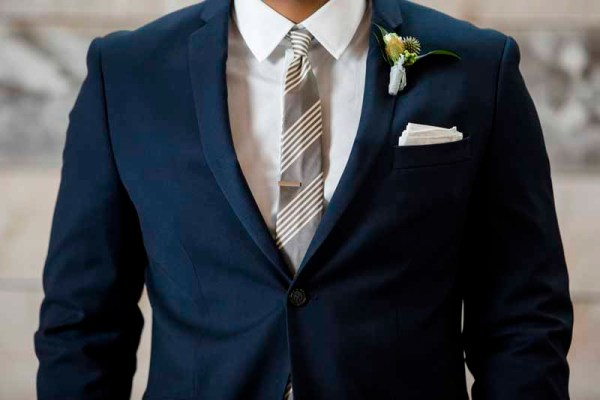 Groom in navy suit, gray tie, thistle boutonniere for West Texas wedding style shoot featuring florist Jessica Ormond Events. Caitlin and Ryan Photography.
