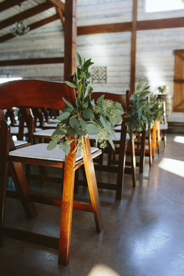 Wedding aisle greenery on wooden chairs designed by west Texas florist Jessica Ormond Events. Ashley J Photography.