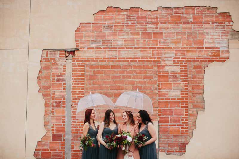 Bride and Bridesmaids under clear umbrellas near brick wall. Downtown winter wedding in Lubbock. Texas wedding photographer, Photo by Betsy. Wedding planner Jessica Ormond Events. Flowers by Dayspring Design.