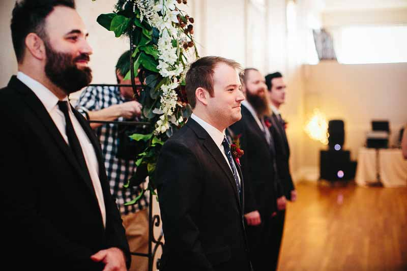 Groom watching bride come down the aisle. Downtown Lubbock wedding at historic Watson Building. Photo by Betsy. Wedding planner Jessica Ormond Events,
