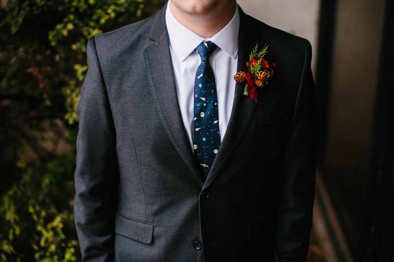 Groom in a space tie with winter boutonniere. Downtown Lubbock December wedding. Photo by Betsy. Wedding planner Jessica Ormond Events,