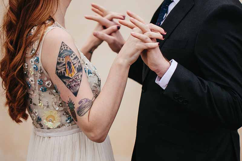 Couple's hands intertwined during first look. Tattooed bride. Wedding Planner Jessica Ormond Events. Photo by Betsy.