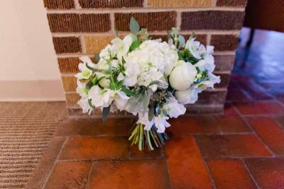 White hand-tied winter bridal bouquet of Hellebore, Veronica, Sweet Pea, and Hydrangea designed by Texas wedding florist Jessica Ormond Events. Photography by Tara Hobgood.
