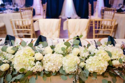 Elegant winter wedding head table with hydrangea, rose, and eucalyptus runner at Legacy Event Center in Lubbock. Designed by Texas florist Jessica Ormond Events. Photo by Tara Hobgood Photography.
