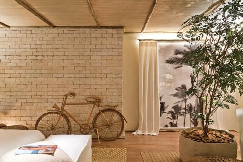 parede tijolo aparente, paleta de cor neutra para quarto, teto de madeira, planta dentro de casa, bicicleta