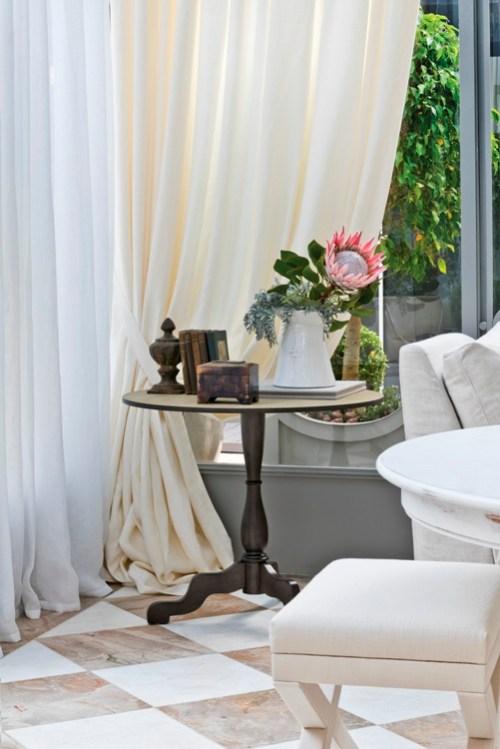 mesa lateral com vaso branco regador, cortinas de linho nude bege neutra