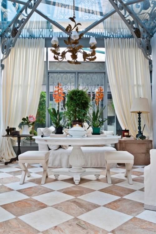 lustre abajur branco, piso quadriculado, plantas dentro de casa, cortina de linho bege, mesa central redonda branca, estufa, jardim de inverno