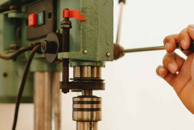 crop person working with drill press