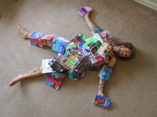 Joshua Samuel Brown naked beneath a pile of books hes written.