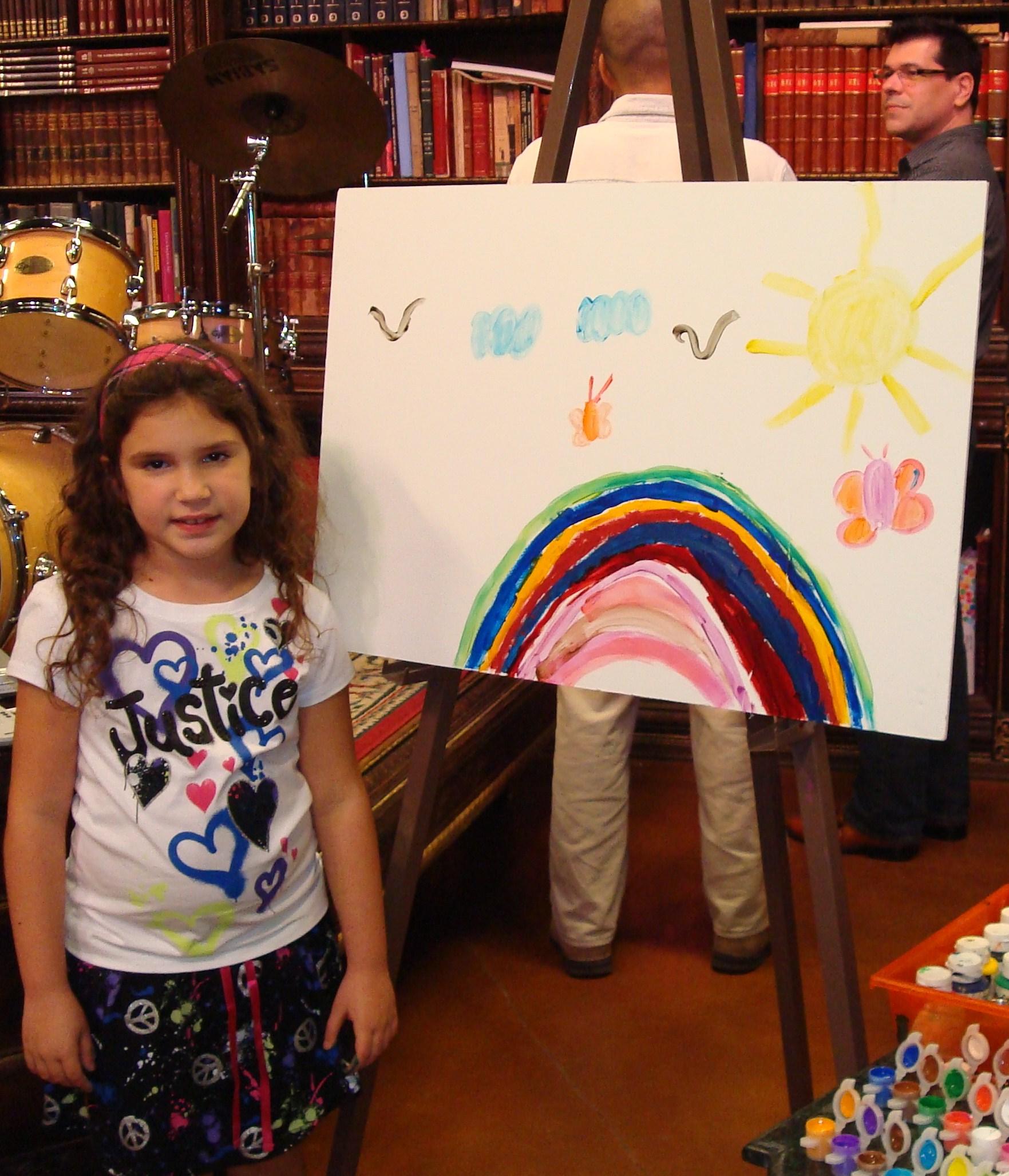La niña Melisa Ortiz, mostrando su dibujo, y el bloguero Eddy Díaz Souza detrás, del blog Artedfactus.