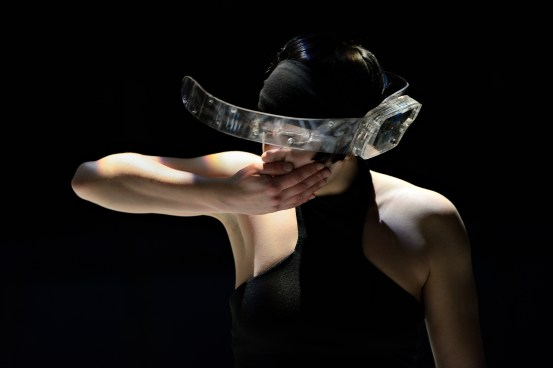 Dancer Sophie Breton wearing the Visor digital musical instrument during a performance of Les Gestes. Instrument design by Joseph Malloch and Ian Hattwick. Photograph by Michael Slobodian. Credit: Van Grimde Corps Secrets / IDMIL / CIRMMT / McGill University.