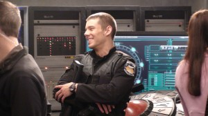 A smiling Brian J. Smith (Lieutenant Matthew Scott) in the control room at Icarus Base