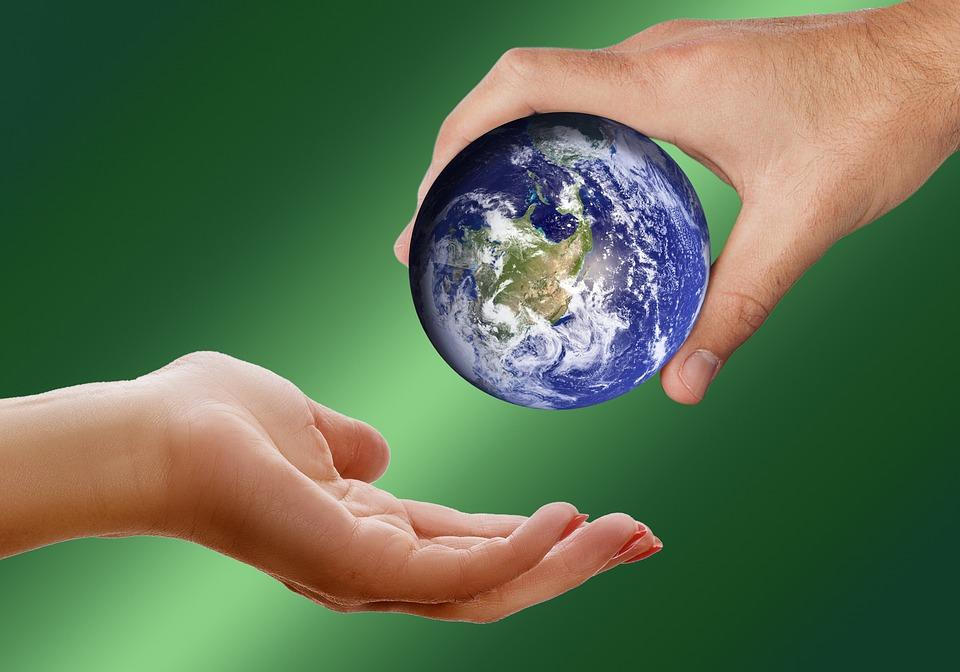 Un planeta Tierra de tamaño reducido que es entregado por la mano de un hombre a la de una mujer.