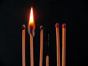 imagen en la que se ven varios fósforos verticales en hilera, unos sin usar, otros ya usados y uno quemándose.