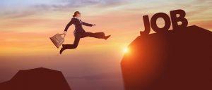 """Una mujer salta entre dos montañas simuladas ante una puesta del sol, en la que la montaña a la que llegara dice trabajo en inglés, """"JOB"""""""