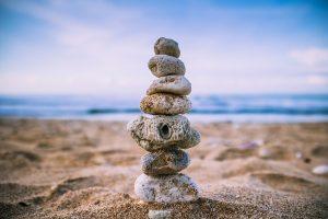 Una playa con el océano de fondo y en el primer plano unas piedras amontonadas como una torre guardando el equilibrio