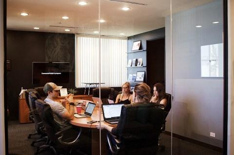 sala de juntas con personas que se encuentran trabajando.