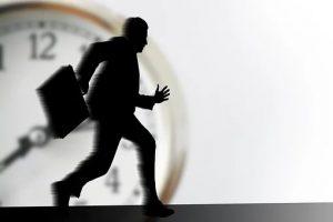 Silueta de hombre corriendo con un portafolio en la mano, y en el fondo un reloj