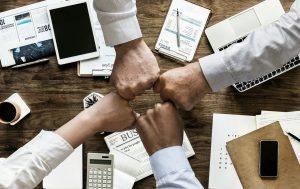 Choque de 4 puños sobre una mesa de trabajo con papeles y equipo de trabajo.