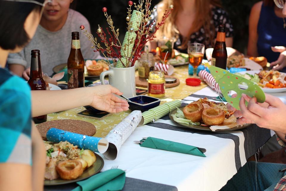 Personas conviviendo alrededor de una mesa con alimentos.