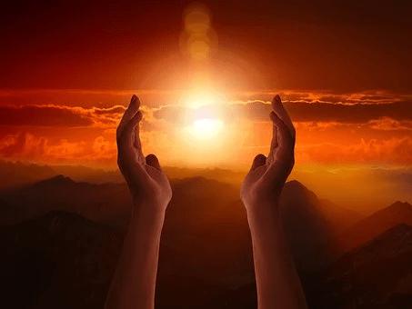 Unas manos así el cielo con el sol entre ellos.