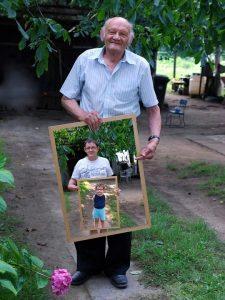 imagen de un abuelo sosteniendo una foto en la que se ve a su hijo sosteniendo una foto de su nieto.