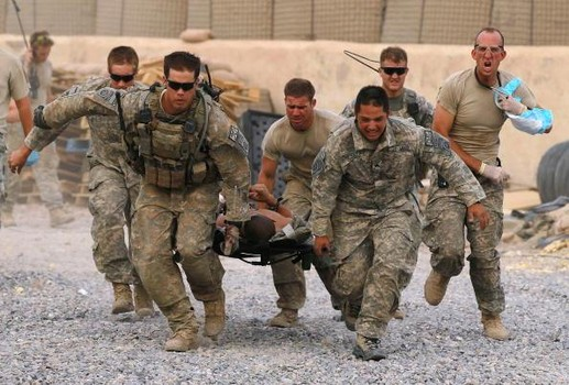 KANDAHAR, AFGHANISTAN - JUNE 24:  U.S. Army soldiers carry a critically wounded American soldier on a stretcher to an awaiting MEDEVAC helicopter from Charlie Co. Sixth Battalion, 101st Airborne Combat Aviation Brigade, Task Force Shadow June 24, 2010 near Kandahar, Afghanistan. As combat operations begin to escalate near Kandahar, the 101st Airborne MEDEVAC unit transports casualties of war as well as sick and injured local residents.  (Photo by Justin Sullivan/Getty Images)