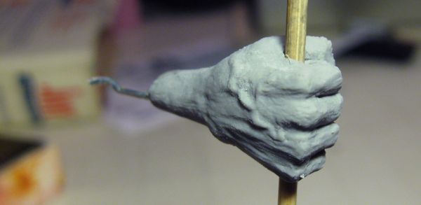 Humanoid sculpture, right hand with a walking stick