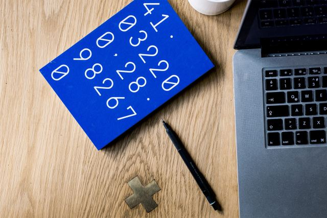 A blue notebook with numbers on its cover on a desk next to a laptop and a pen