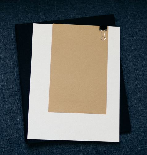 brown-paper-clipped-to-larger-white-paper-on-folder