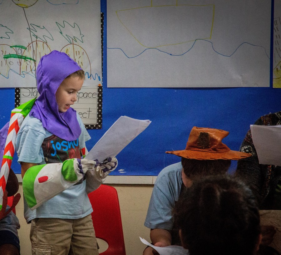child in Buzz Lightyear costume reading lines