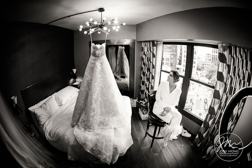 The bride peers over at her beautiful Monique Lhuillier wedding dress hanging from the chandelier.