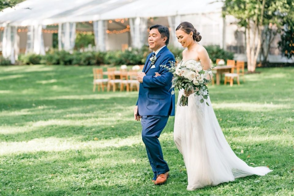 Bride walks with father down aisle photo