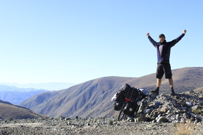 Feeling triumphant after difficult bike touring to the top of the mountain pass in Turkey.
