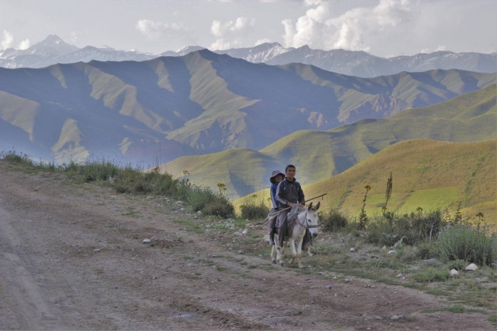 Children ride a donkey in front the tall mountains of Tajikistan on the Pamir Highway,