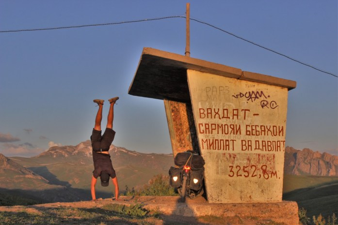 Doing a handstand at the top of the mountain pass at sunset on the Pamir Highway in Tajikistan.