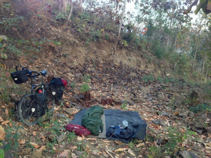 Illegal wild camping in Myanmar. Sleeping mat, sleeping bag and bivvy bag laid out on the jungle floor and bike standing up beside.