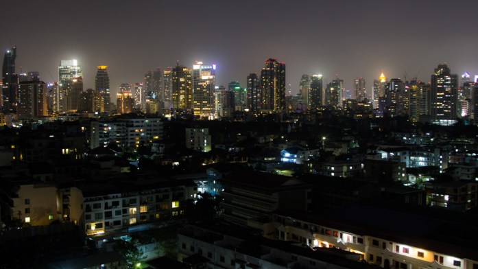 Bangkok Skyline at night. Lit up skyscrapers and buildings with a golden glow from the windows against the dark night.