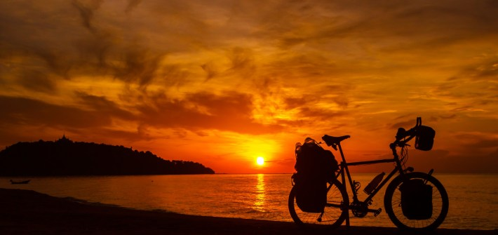 Silhouette of a bike on a beach in Thailand at sunset with a beautiful orange sky.