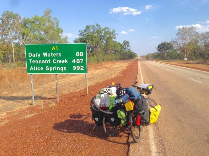 Two touring bikes lent together in the Australia outback in front of a sign for Alice Springs and Tennant Creek and Daly Waters