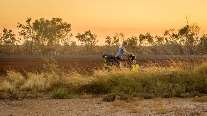 Sunrise in Australia Outback as touring cyclist pushes bicycle back to the road.