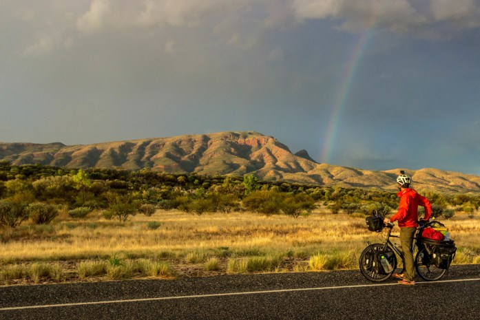 Rainbow arches over West MacDonnell Mountain Range in Outback Australia