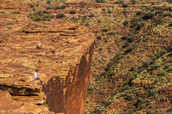 Sitting with leg's dangling on the rim at the edge of King's Canyon in Australia