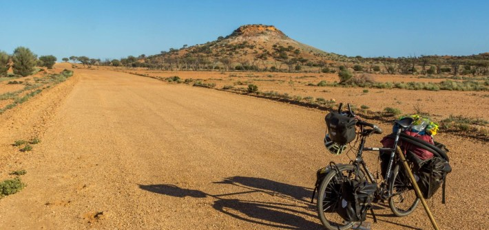 A loaded touring bike on the centre of an unsealed road in Australian Outback on Oodnadatta Track