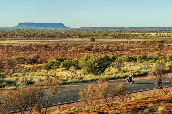 A cyclist rides past Mount Conner on the horizon.